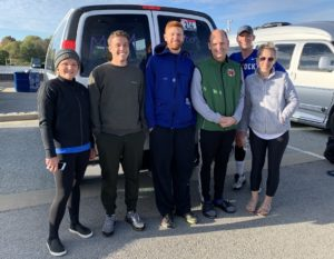 A group of friends standing in front a van in running gear.