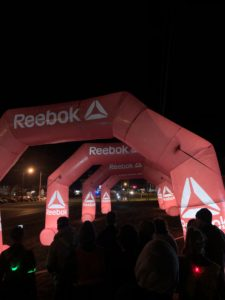A shot of runners at night with bright start arches