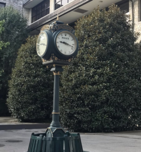 Green and gold Rolex clock on a lamp post.